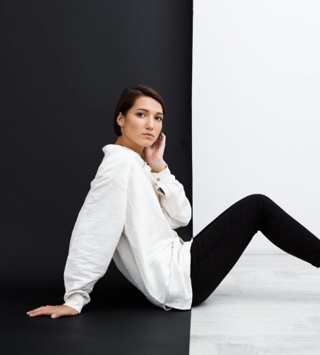 Young beautiful brunette girl looking at camera sitting on floor over black and white background. Copy space.